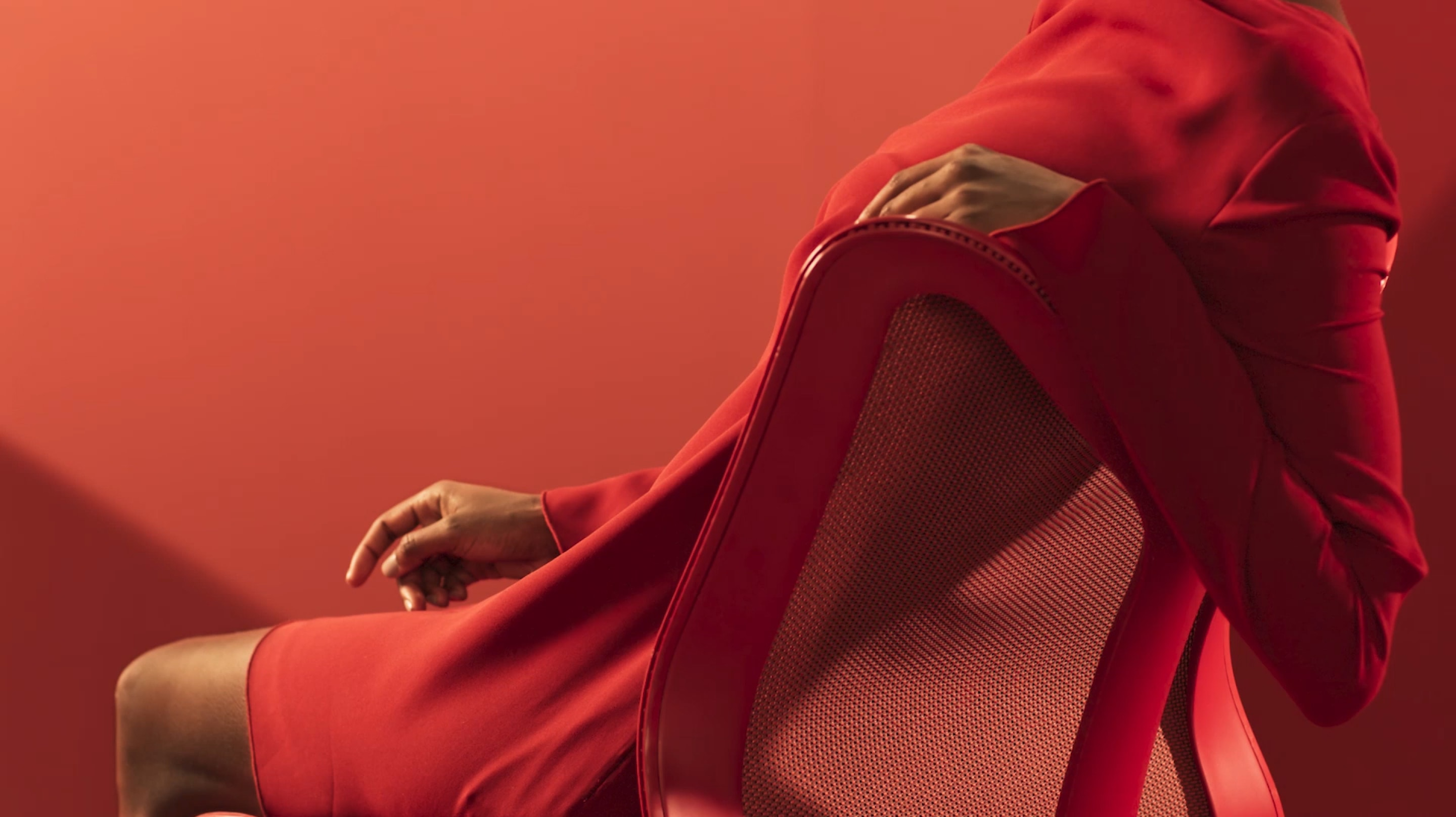 A woman in a red dress reclines with her arm over the backrest of a Canyon red Cosm Chair.