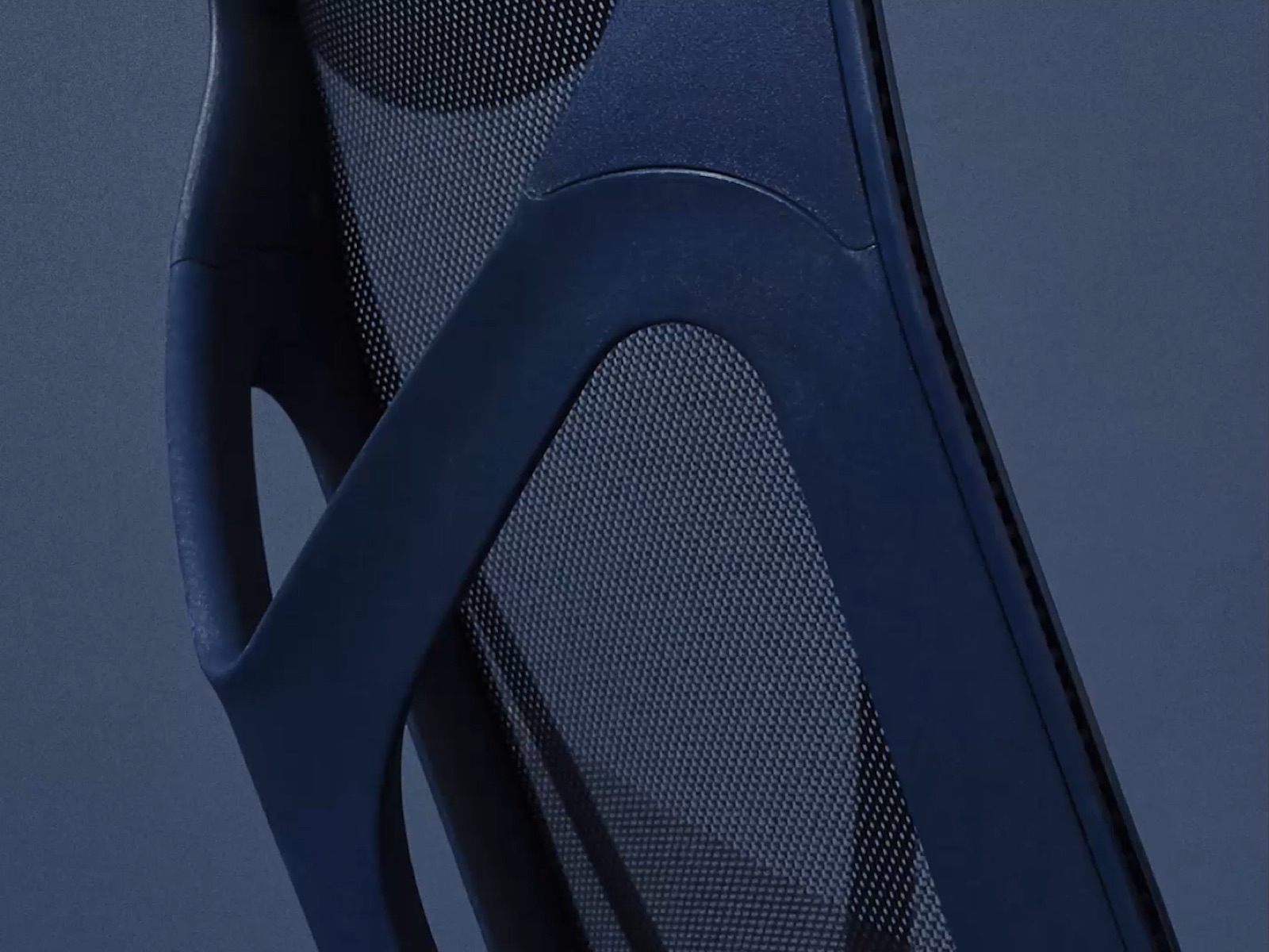 A close-up from behind of the frame of a Nightfall dark blue Cosm ergonomic desk chair.