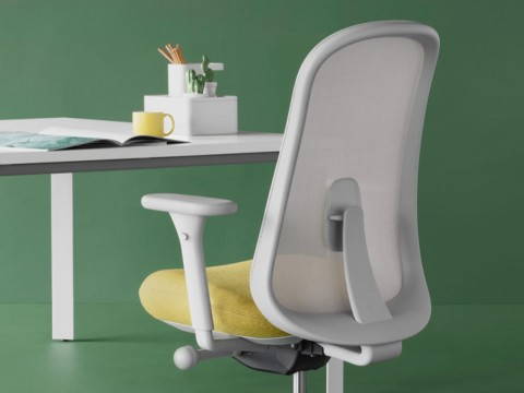 Grey and yellow Lino Chair in front of a desk with accessories, viewed from the back at an angle.