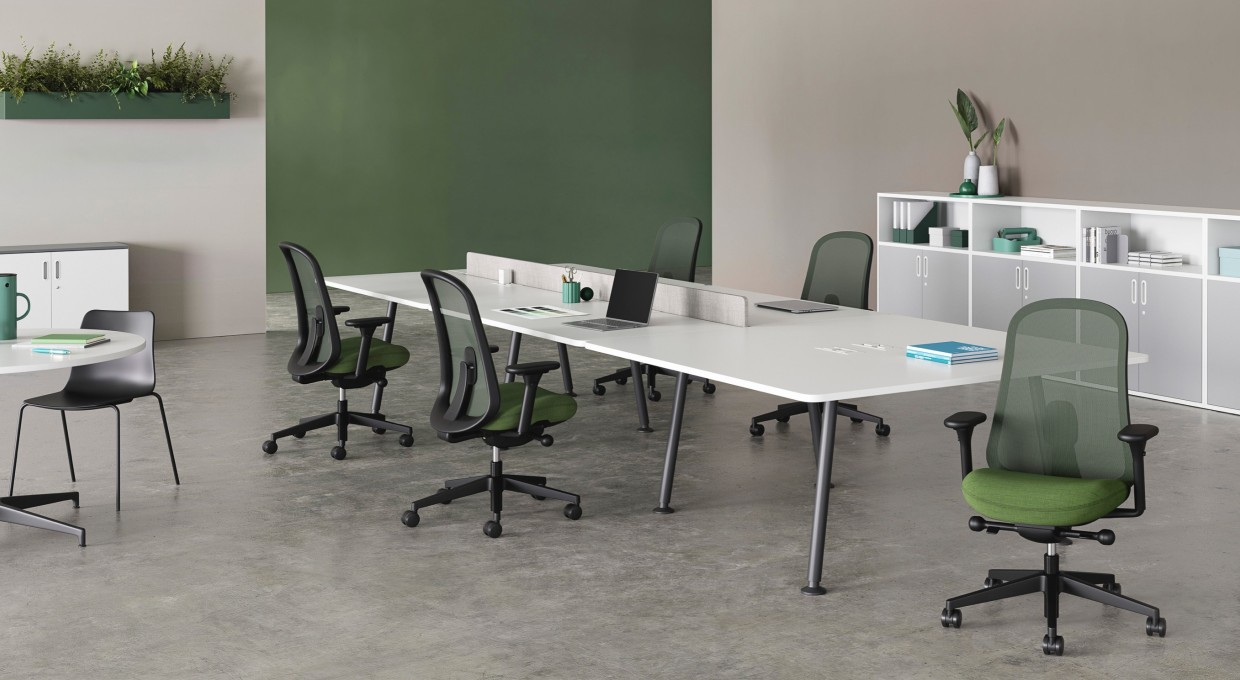 Five black and green Lino Chairs positioned around a large Memo desk. Paragraph units provide storage options around the room with a white Civic Table offering an alternative workspace.